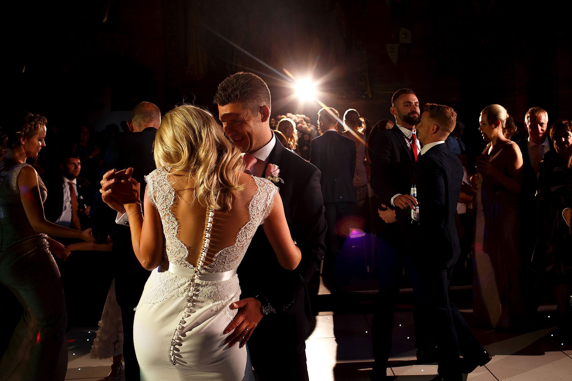 Bride with blonde hair and buttons all the way down the back of wedding dress dancing together on the dance floor | Peckforton Castle Wedding by Toni Darcy Photography