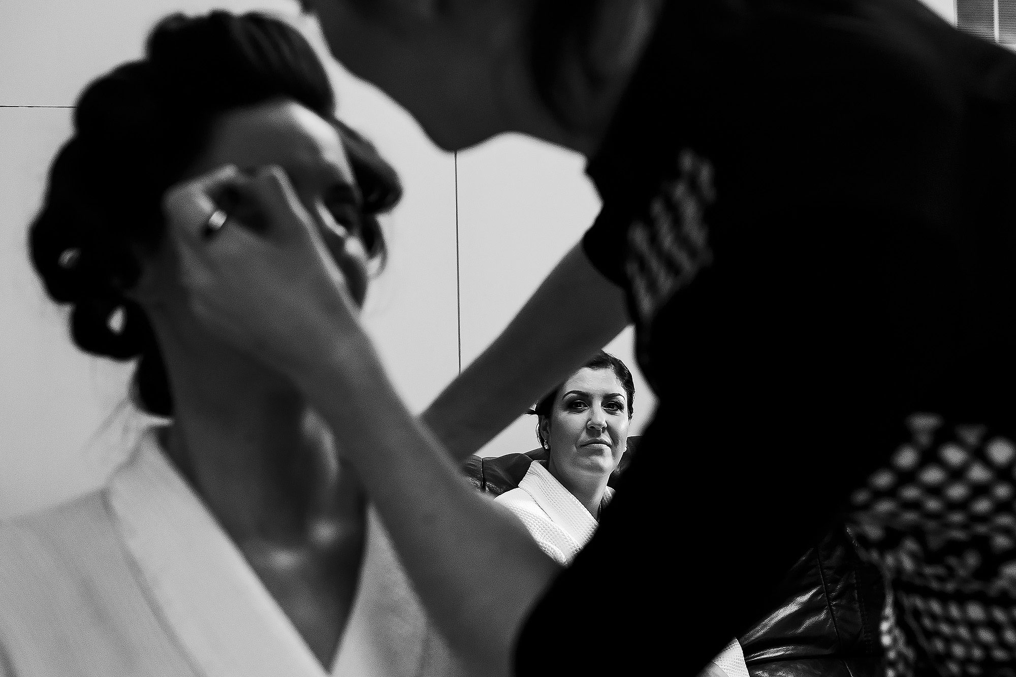 Bride having make up applied on the morning of her bridesmaids watch in the distance | Summer wedding at Wellbeing Farm - Toni Darcy Photography