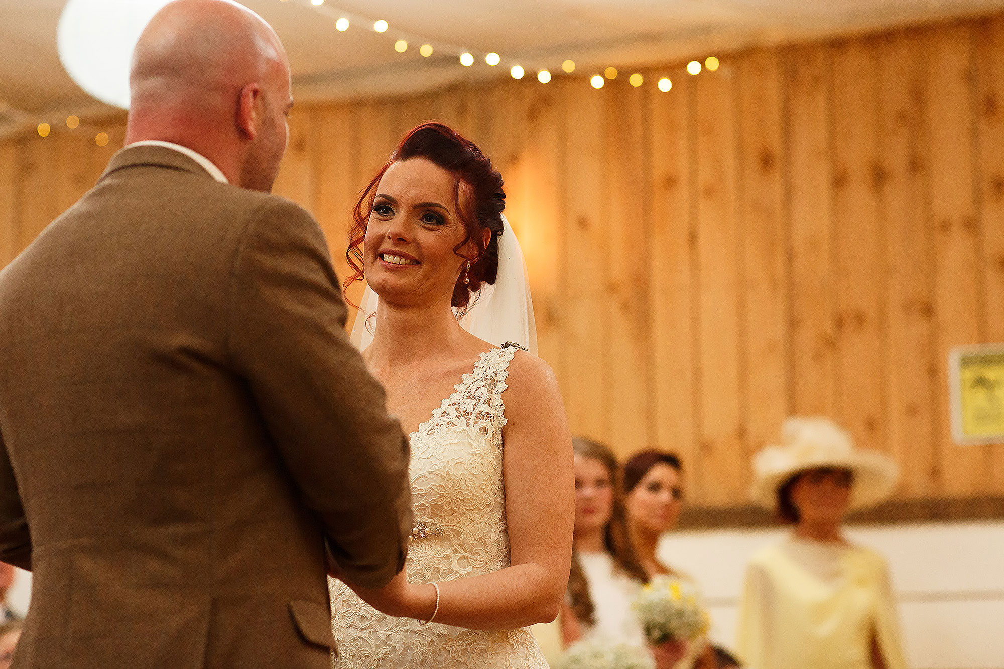 Bride with red hair and lace dress looking into the eyes of her groom during the wedding ceremony | Summer wedding at Wellbeing Farm - Toni Darcy Photography
