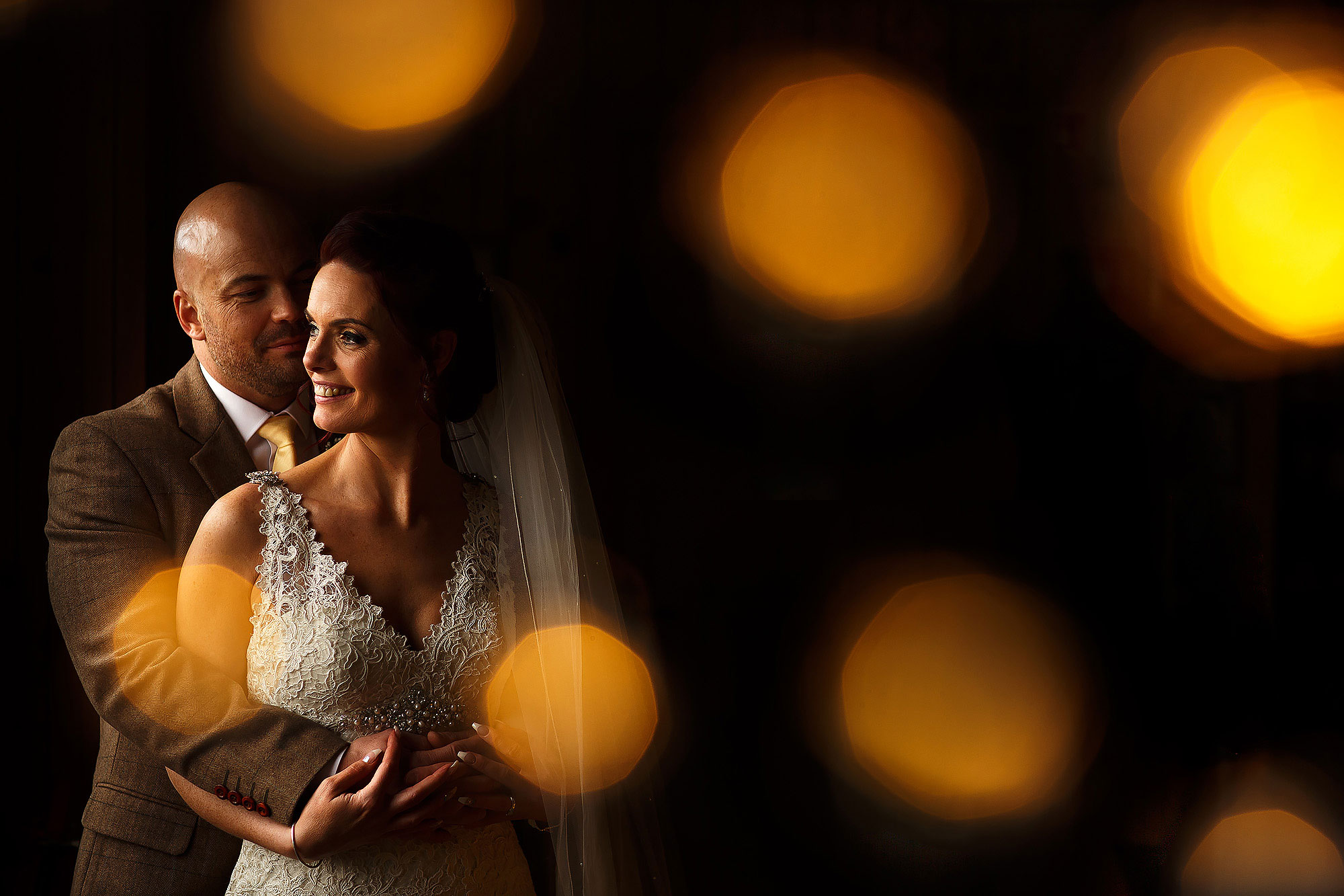 Bride and groom in beautiful window light. Bride wearing lace wedding dress, groom wearing tweed brown suit | Summer wedding at Wellbeing Farm - Toni Darcy Photography