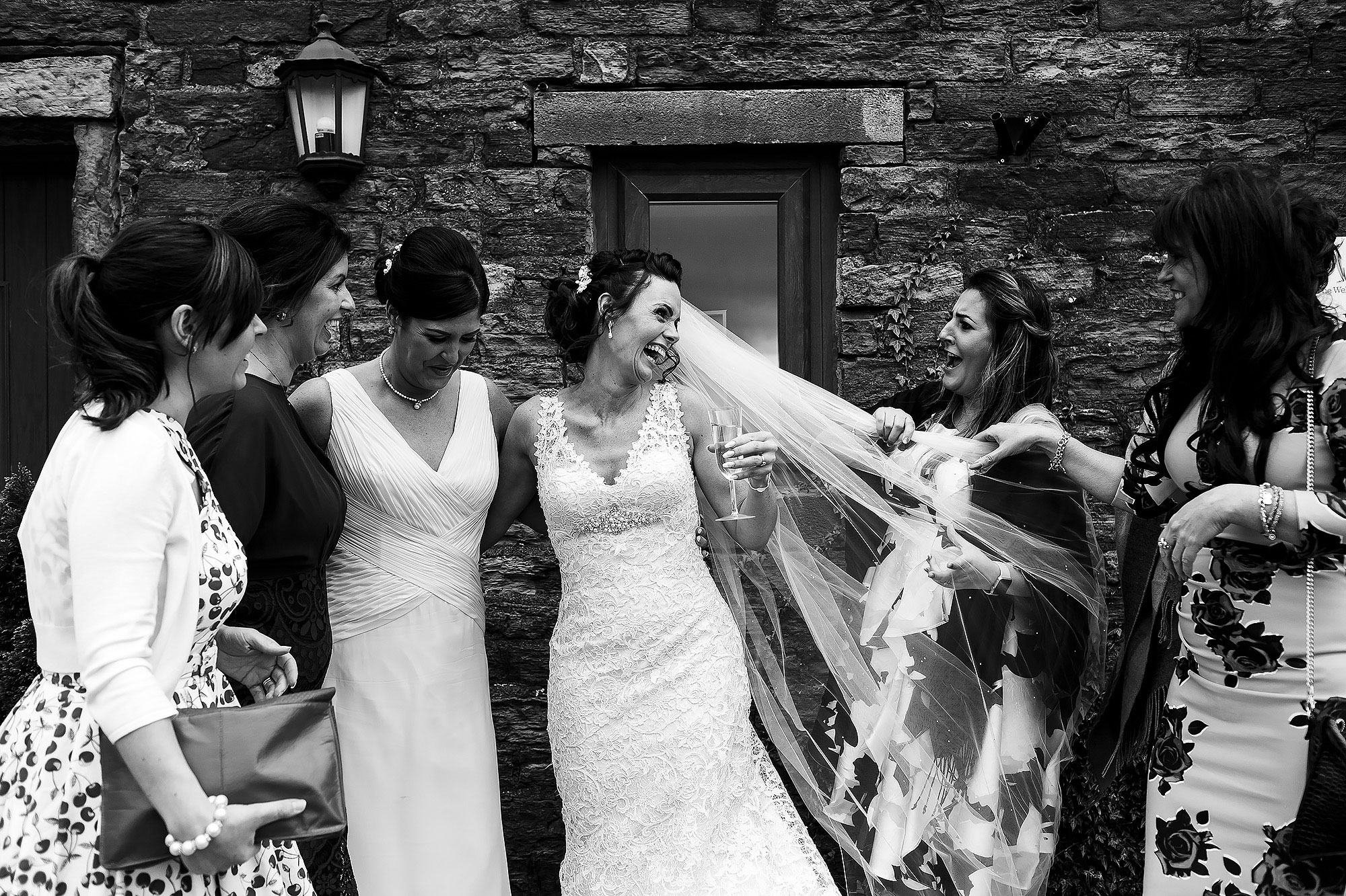 Bride laughing with best friends outside stone building | Summer wedding at Wellbeing Farm - Toni Darcy Photography