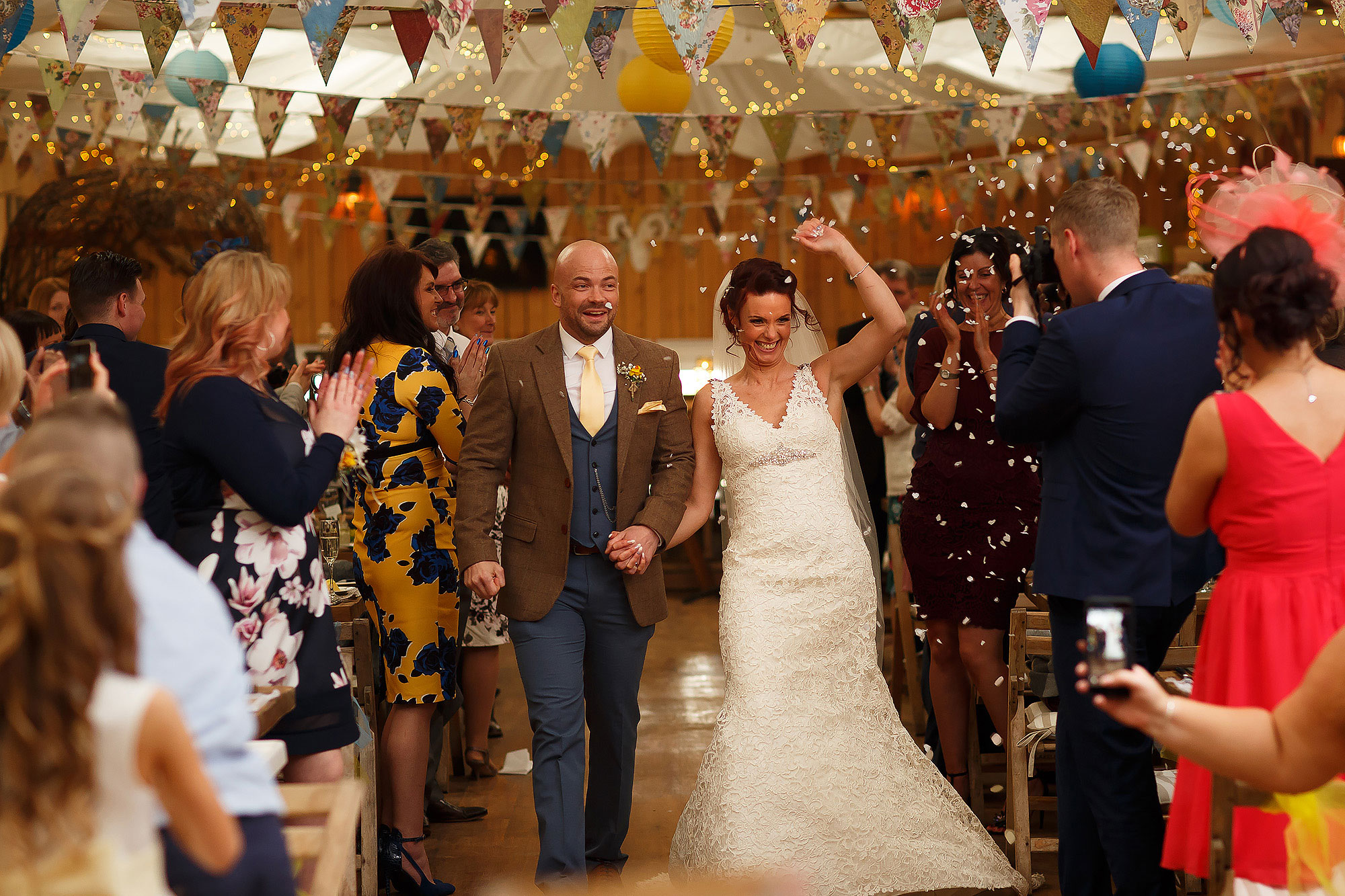 Bride and groom walking down the aisle as guests throw confetti | Summer wedding at Wellbeing Farm - Toni Darcy Photography