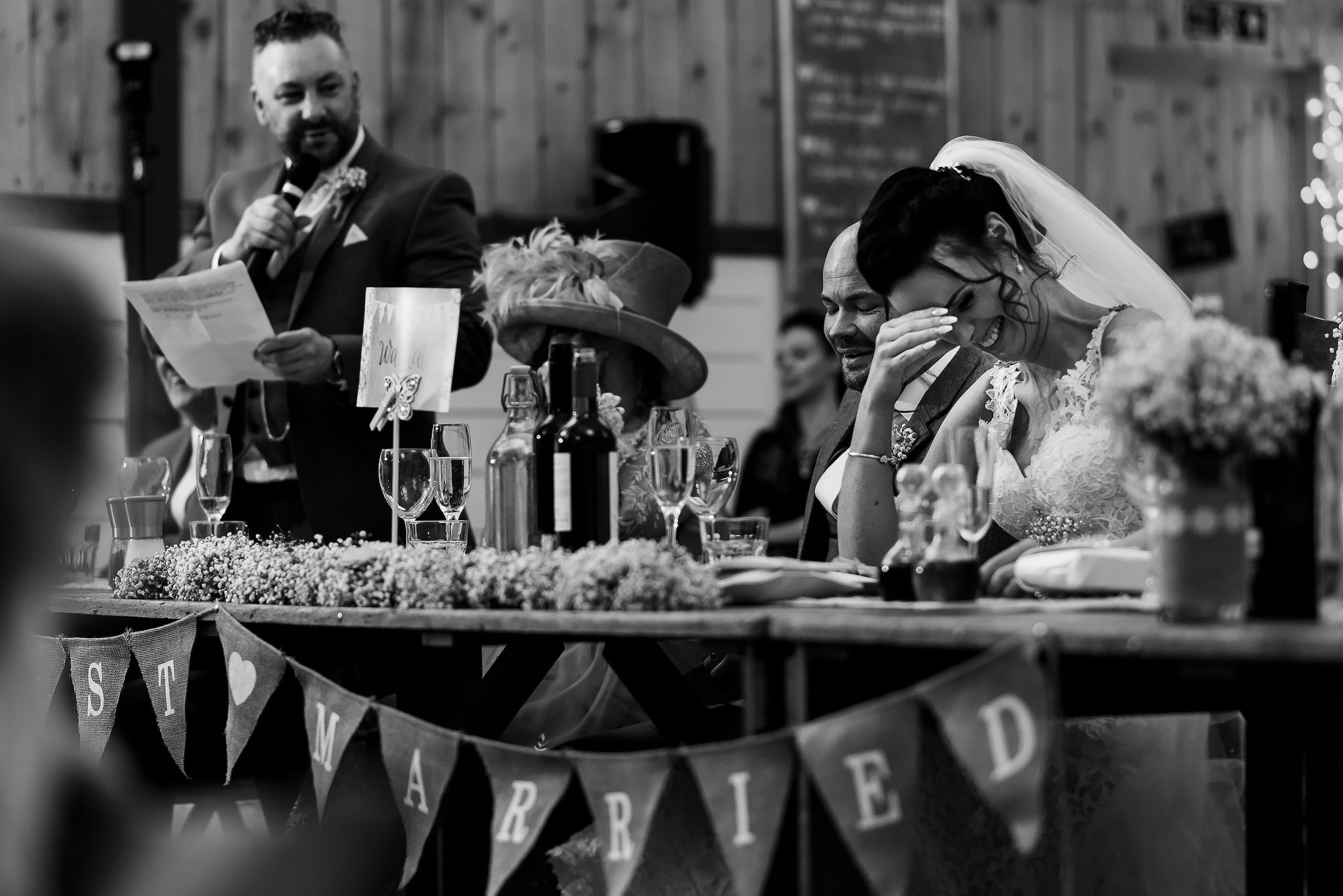 Bride holding her head in her hands during the best mans speech | Summer wedding at Wellbeing Farm - Toni Darcy Photography