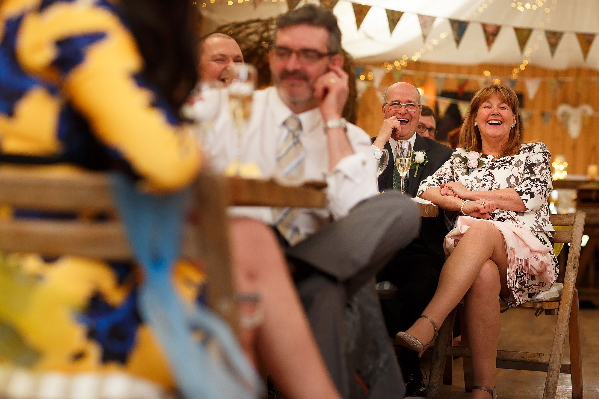 Wedding guests laughing during the wedding speeches | Summer wedding at Wellbeing Farm - Toni Darcy Photography