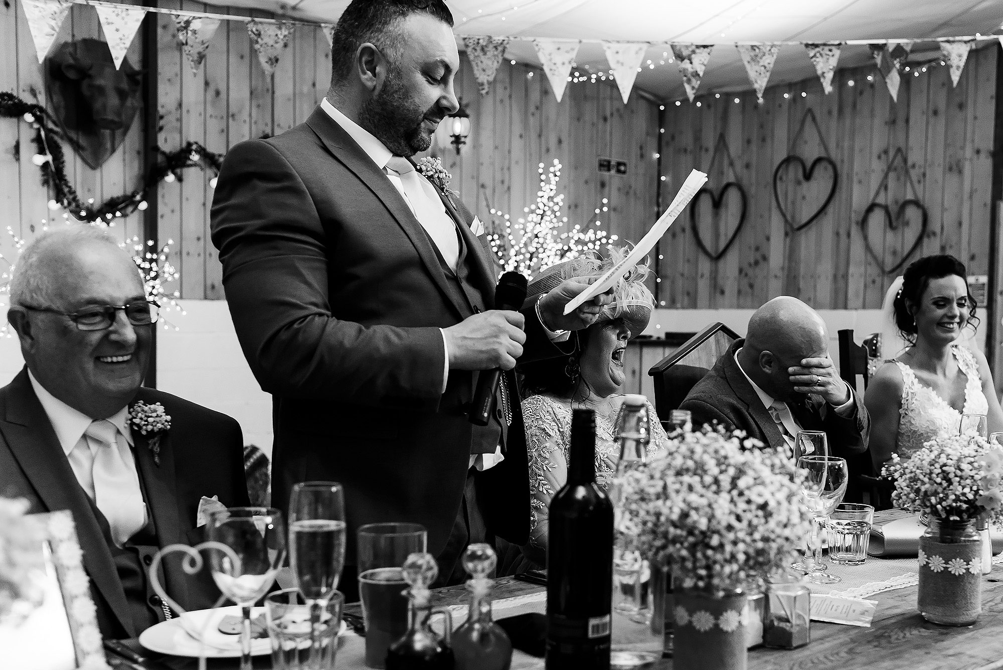 Groom holding head in his hands as the best man delivers his speech | Summer wedding at Wellbeing Farm - Toni Darcy Photography