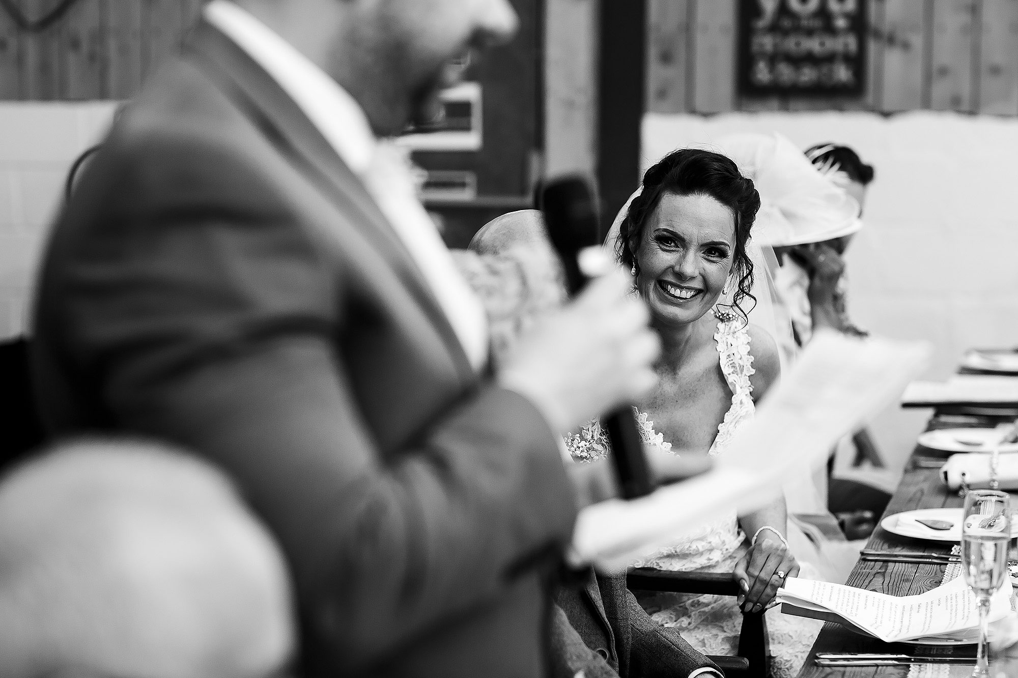 Bride looking towards the groom as he gives his wedding speech | Summer wedding at Wellbeing Farm - Toni Darcy Photography