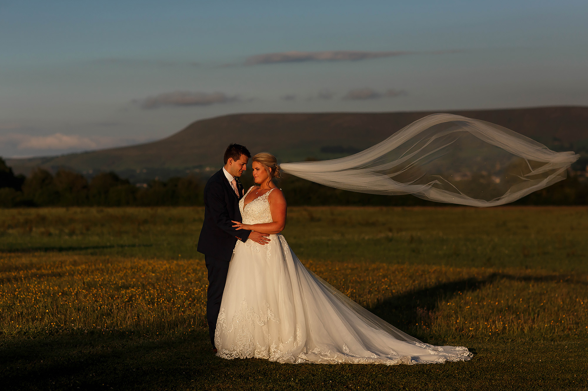 bride and groom in a field with the long veil flowing behind